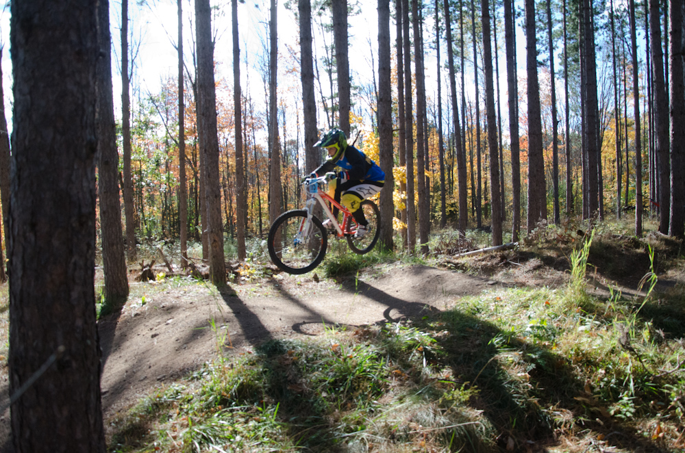 Dual slalom MTB racer airs over jump at the Michigan Tech Trails