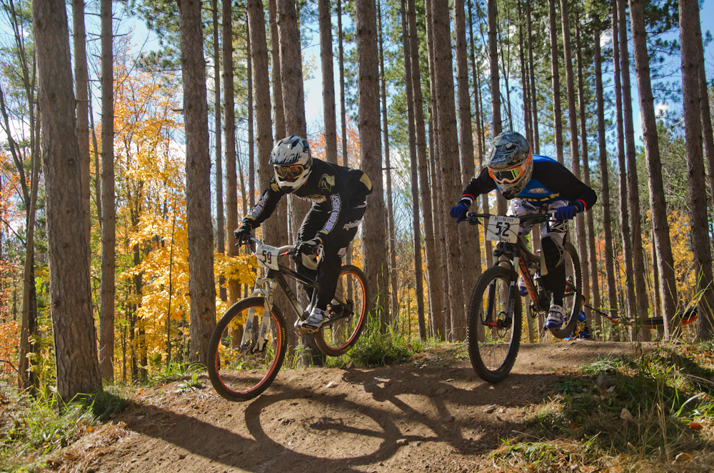 Dual slalom MTB racers air over jump head-to-head at the Michigan Tech Trails