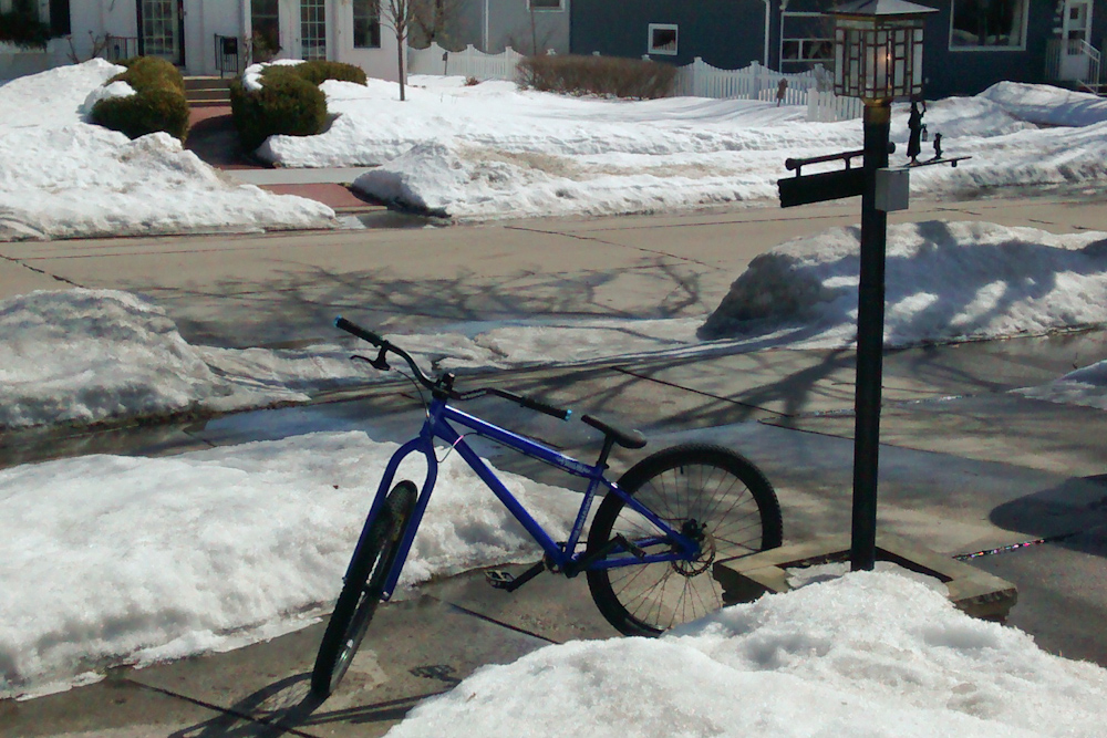 My dirtjumping bike leaning against a planter with snow all around