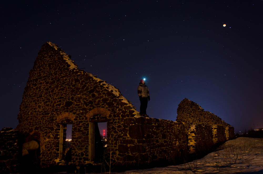 Night picture of Bryan on top of mining ruins with the eclipse in the background
