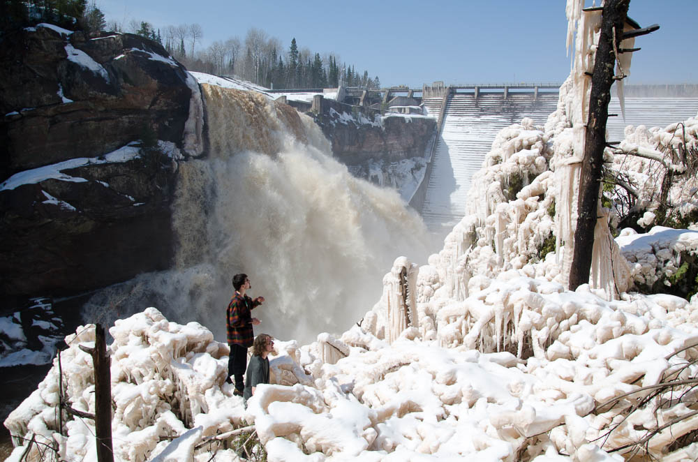 Two OVC members climbing over ice covered trees with a rushing spillway in the background